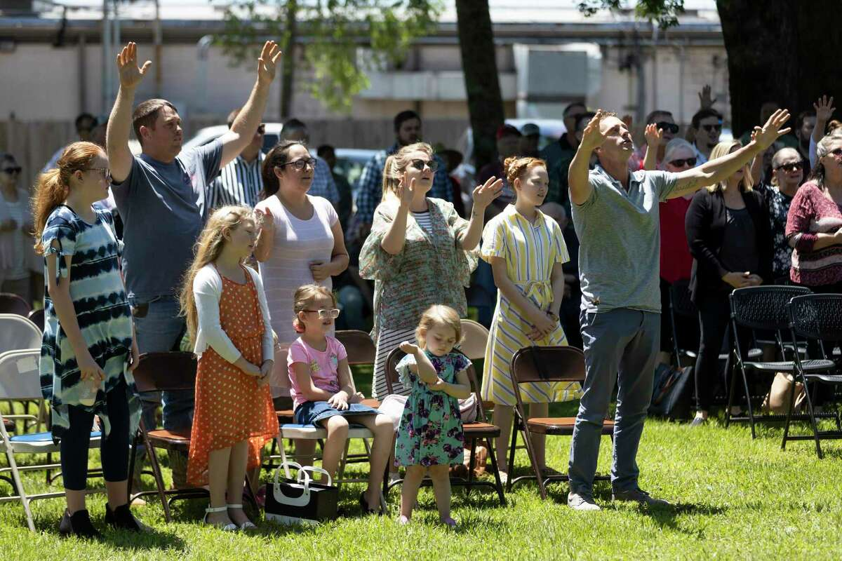 Dozens of attendees participate in a prayer during a National Day of Prayer celebration behind Montgomery County Justice of Peace Precinct 1, Thursdayin Willis. Local faith leaders and politicians spoke at this year's event