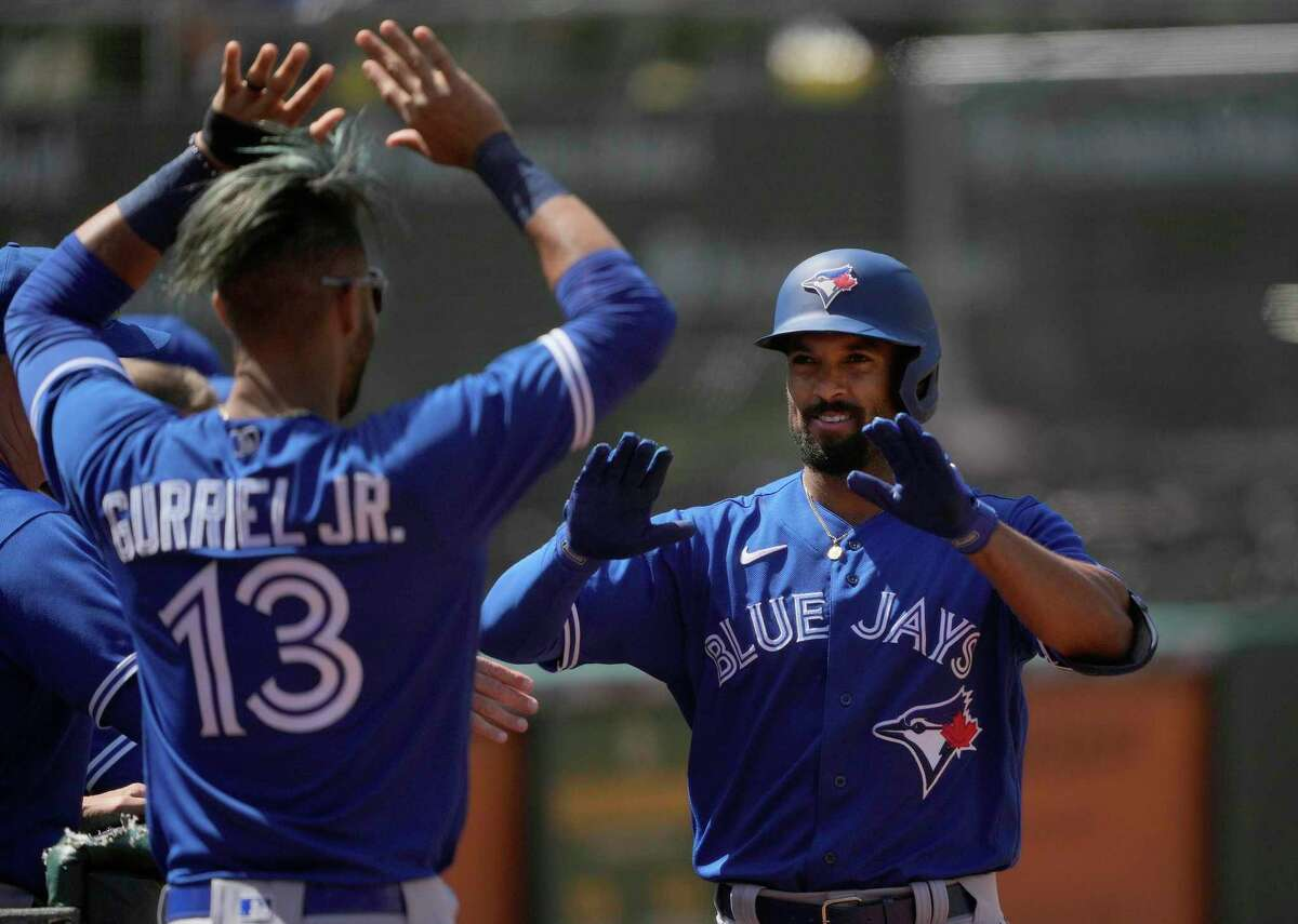 Toronto's Marcus Semien (right) celebrates with Lourdes Gurriel Jr. after hitting a solo home run at the Coliseum.