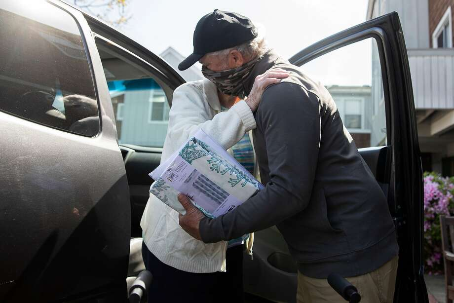 David Mann helps his mother, Marjorie Mann, 94, exit his car at Waters Edge Lodge in Alameda after taking her on their first in-person outing, to Kohl's. Photo: Jessica Christian/The Chronicle