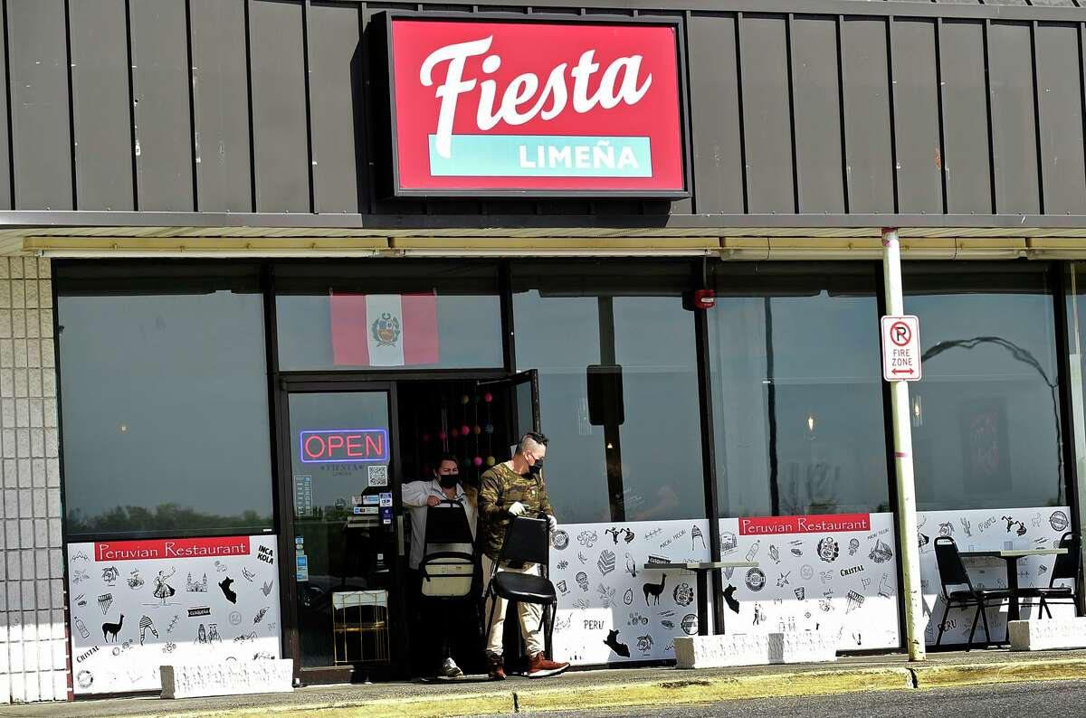 Staff of Fiesta Limena put chairs and table outside Thursday in Norwalk.