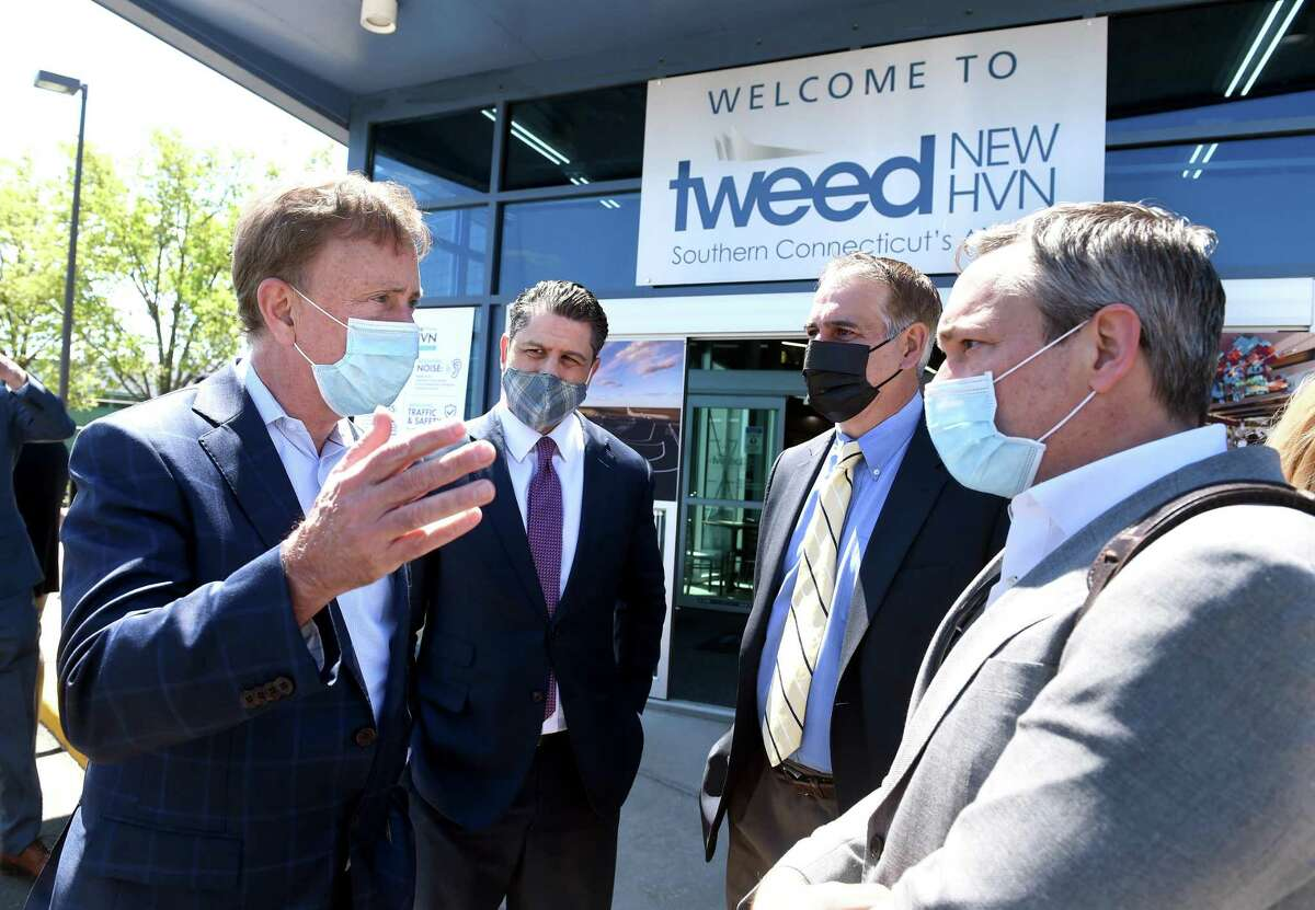 From left, Governor Ned Lamont, Avports CEO Jorge Roberts, John Picard, chairman of the Tweed New Haven Airport Authority and Avports board member Johathan Hunt speak after a press conference announcing major expansion plans at Tweed New Haven Regional Airport on May 6, 2021.