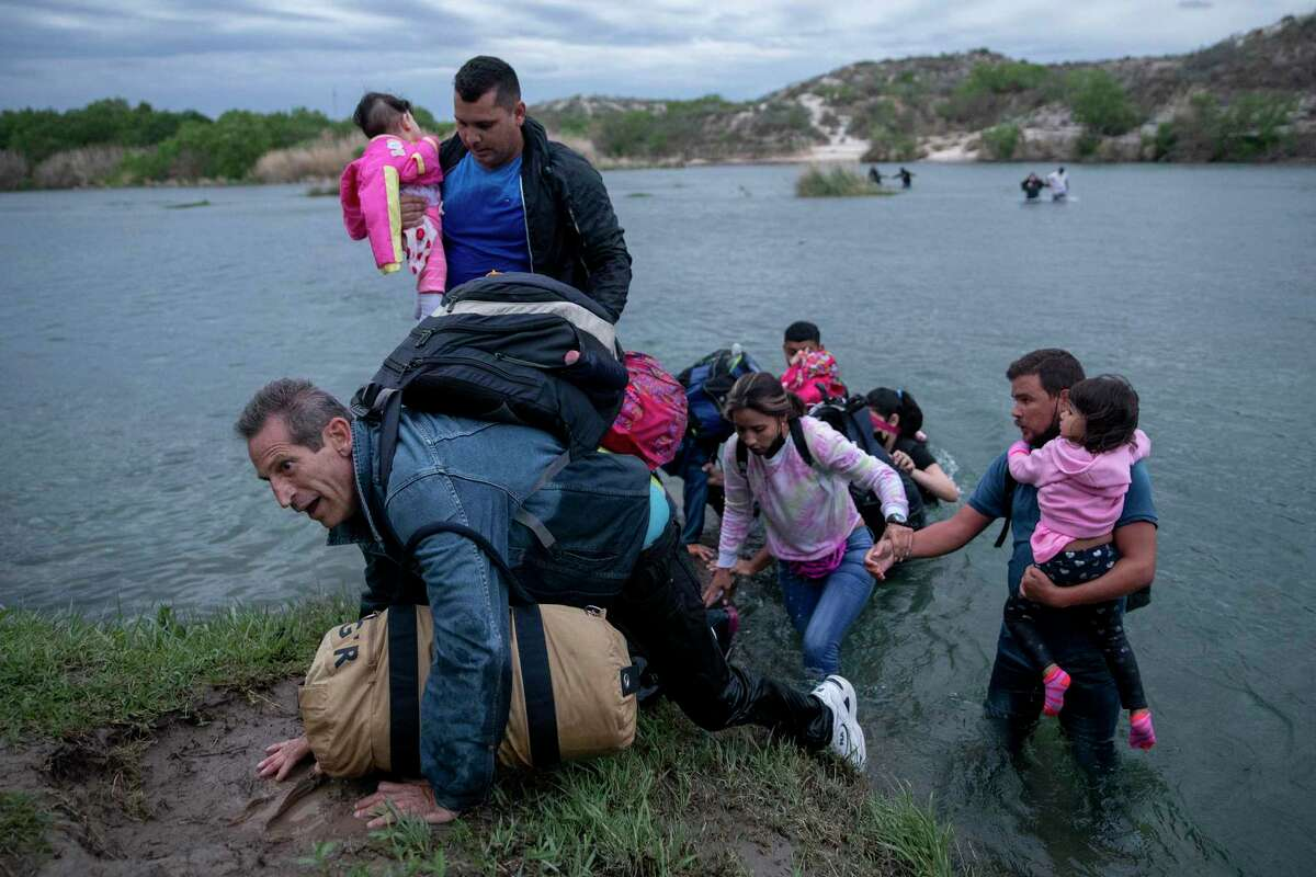 A large group of migrants from Venezuela cross the Rio Grande near Del Rio. The U.S. has granted Venezuelansalready in the country temporary protection from deportations because of the economic collapse and violence in their country.