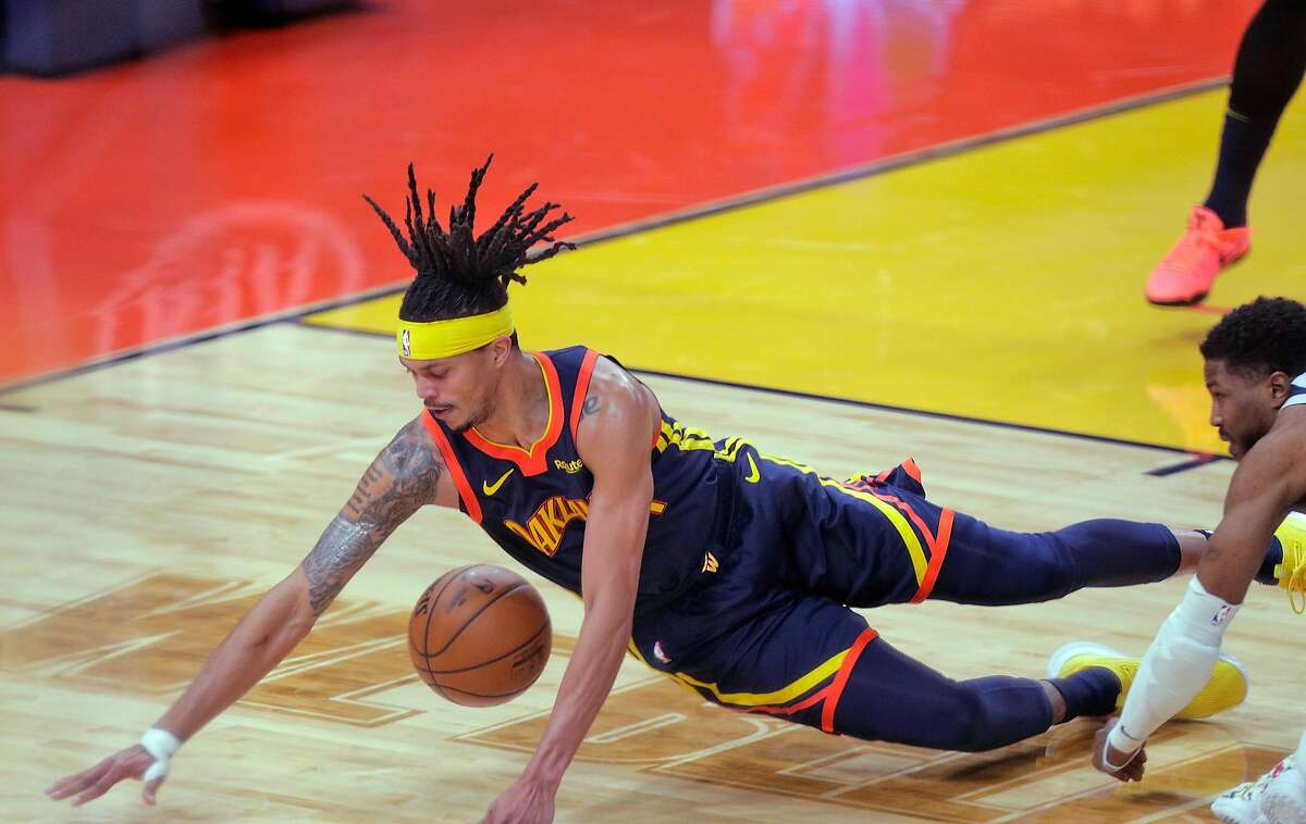 Damion Lee (1) dives for aloose ball in the second half as the Golden State Warriors played the Minnesota Timberwolves at Chase Center in San Francisco, Calif., on Monday, January 25, 2021.