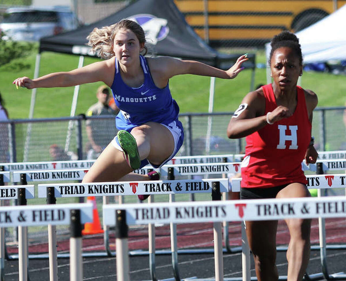 Marquette Catholic's Tristan Fraley (left) clears a hurdle behind Highland's Tanille Thompson during a 100-meters hurdles heat Wednesday at the Triad Invite in Troy.