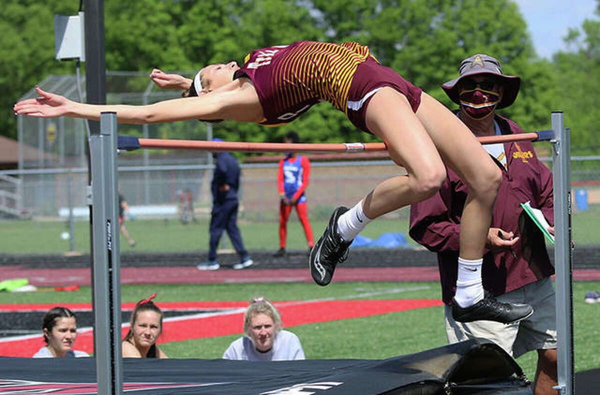 EA-WR's Hannah Sechrest has her leg graze the bar in the high jump while Oilers jumps coach Steve Tyler watches in his role as event runner Wednesday at the Triad Invitational girls track meet in Troy. Sechrest won the high jump and long jump to join teammate Jayden Ulrich as a double winner at the invite. Mascoutah won the 15-team meet, with Belleville West placing runner-up.