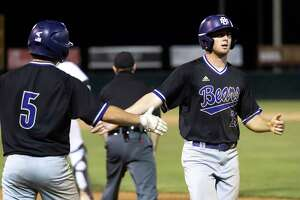 Chase Davis #25 of Montgomery celebrates with teammate Tristan Peterson #5 after scoring during in the sixth inning in Game 1 of the Region III-5A bi-district baseball series against Magnolia at Magnolia High School, Thursday, May 6, 2021, in Magnolia.