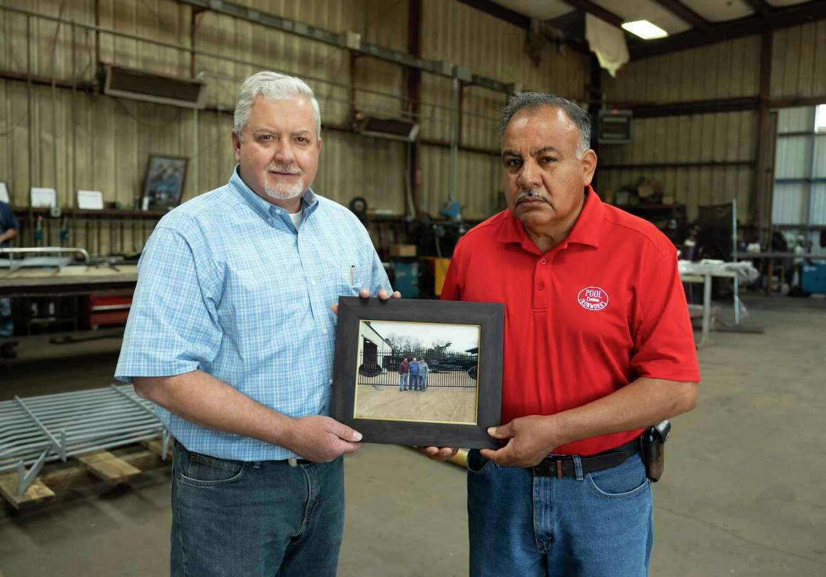 Dusty Adams, left and Freddy Betancourt, co-owners of Pool Custom Ironworks, holds a photo as they pose for a portrait, Wednesday, May 5, 2021, in Conroe. The company will be celebrating it's 50th anniversary of opening this Saturday.