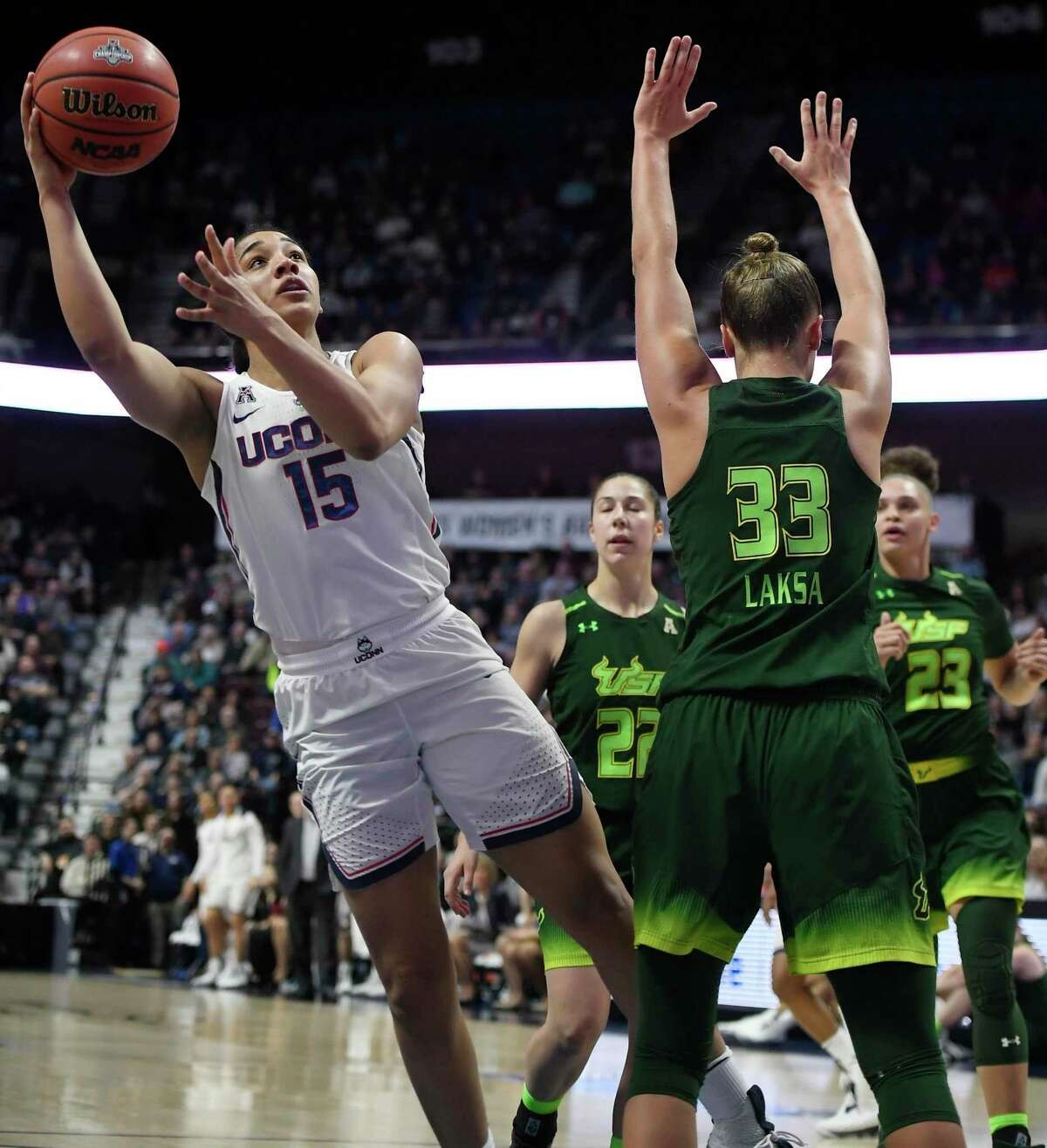 Connecticut's Gabby Williams (15), cuts through the defense of South Florida's Laia Flores (22), Kitija Laksa (33) and Tamara Henshaw (23) for a basket during the first half of an NCAA college basketball game in the American Athletic Conference tournament finals at Mohegan Sun Arena, Tuesday, March 6, 2018, in Uncasville, Conn. (AP Photo/Jessica Hill)