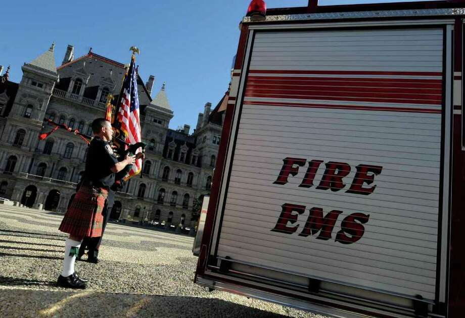 TYhe Albany Fire Department Honor Guard is led by Colonie Police Investigator Chris Smith on bagpipes during a September 11 Remembrance Ceremony at the Empire State Plaza in Albany Saturday morning 9/11/2010. ( Michael P. Farrell / Times Union ) Photo: Michael P. Farrell