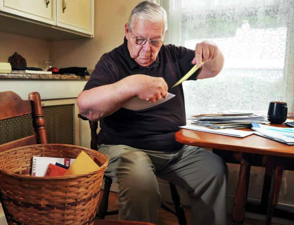 Clifford Ammon sorts through junk mail at his Saratoga Springs home. Some contains advertising, others could be scams. (John Carl D'Annibale / Times Union)