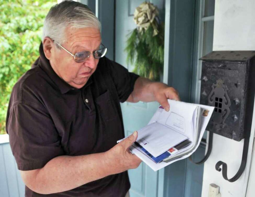Clifford Ammon sorts through mail delivery at his Saratoga Springs home. Some of the offers can be too good to be true. (John Carl D'Annibale / Times Union)