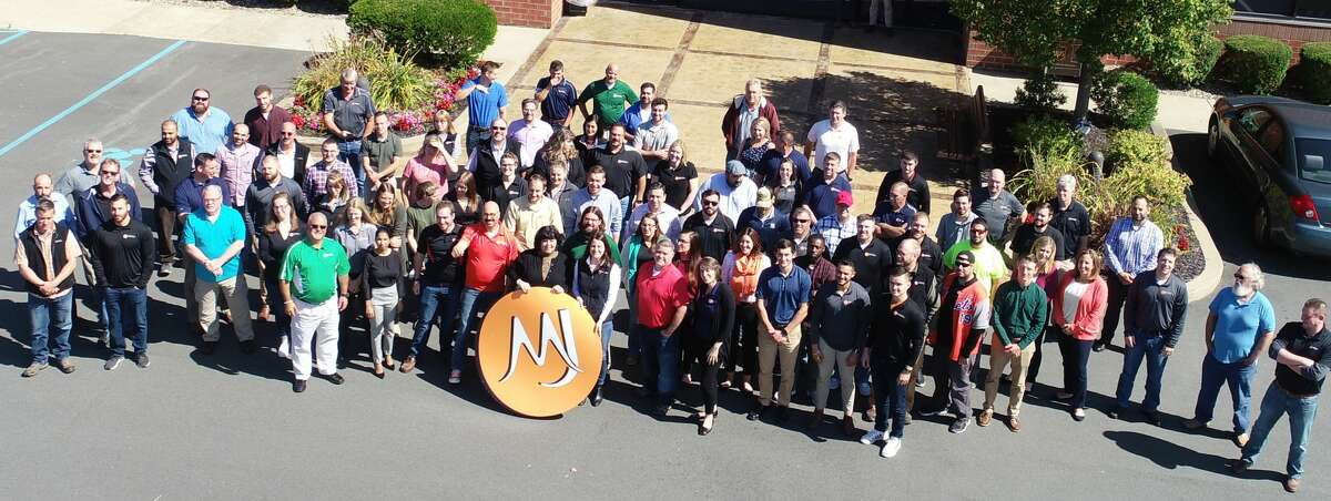 MJ Engineering and Land Survey staff pose in a pre-pandemic photo.