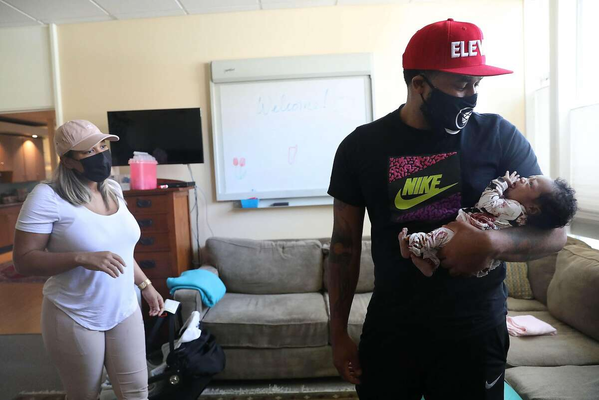 Prentice Powell holds newborn Shai Powell as his wife, Sarai McCall, looks on. Data show Black men such as Prentice, in many aspects, are more attentive to the needs of their young children than fathers from other racial groups.