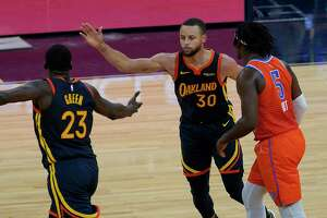 Golden State Warriors forward Draymond Green (23) and guard Stephen Curry (30) celebrate next to Oklahoma City Thunder forward Luguentz Dort (5) during the second half of an NBA basketball game in San Francisco, Thursday, May 6, 2021.
