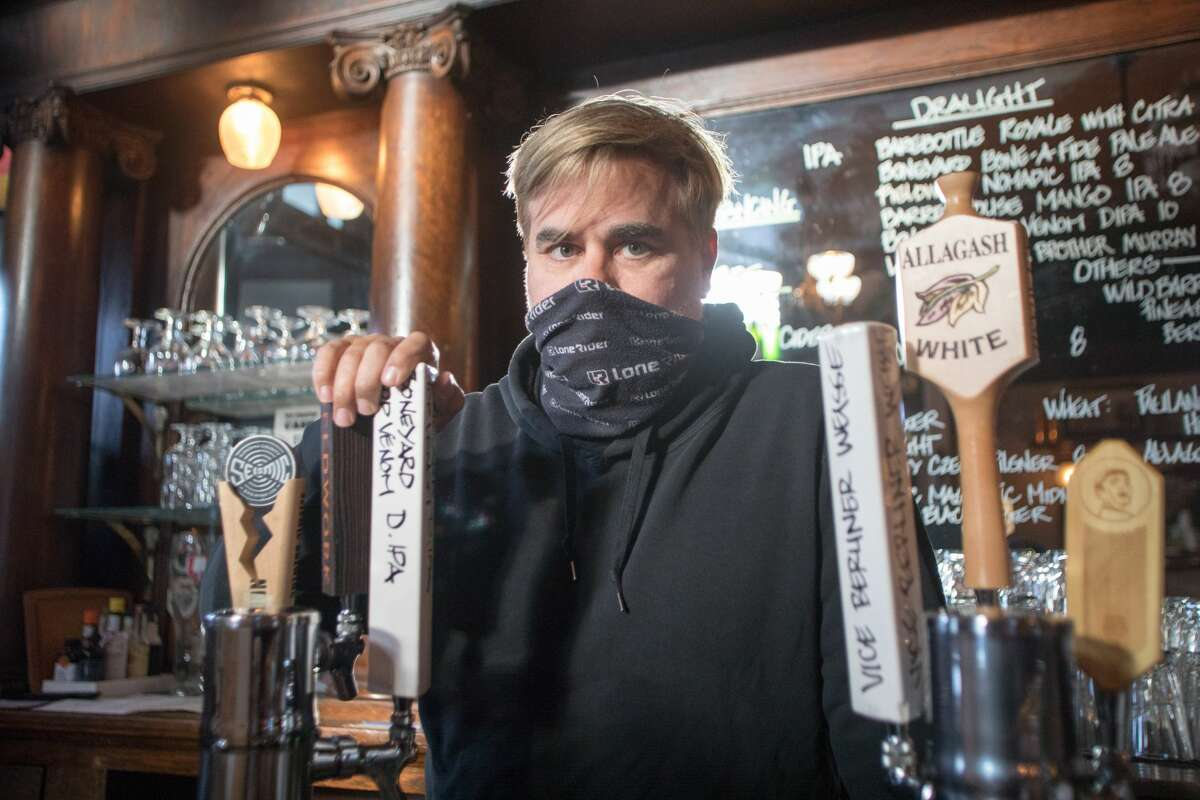 Owner Tom Madonna poses for a photo behind the bar at Shotwell's Saloon in San Francisco on May 6, 2021. For the first time since the COVID-19 shutdown began in March 2020, guests were able to drink in an indoor bar.