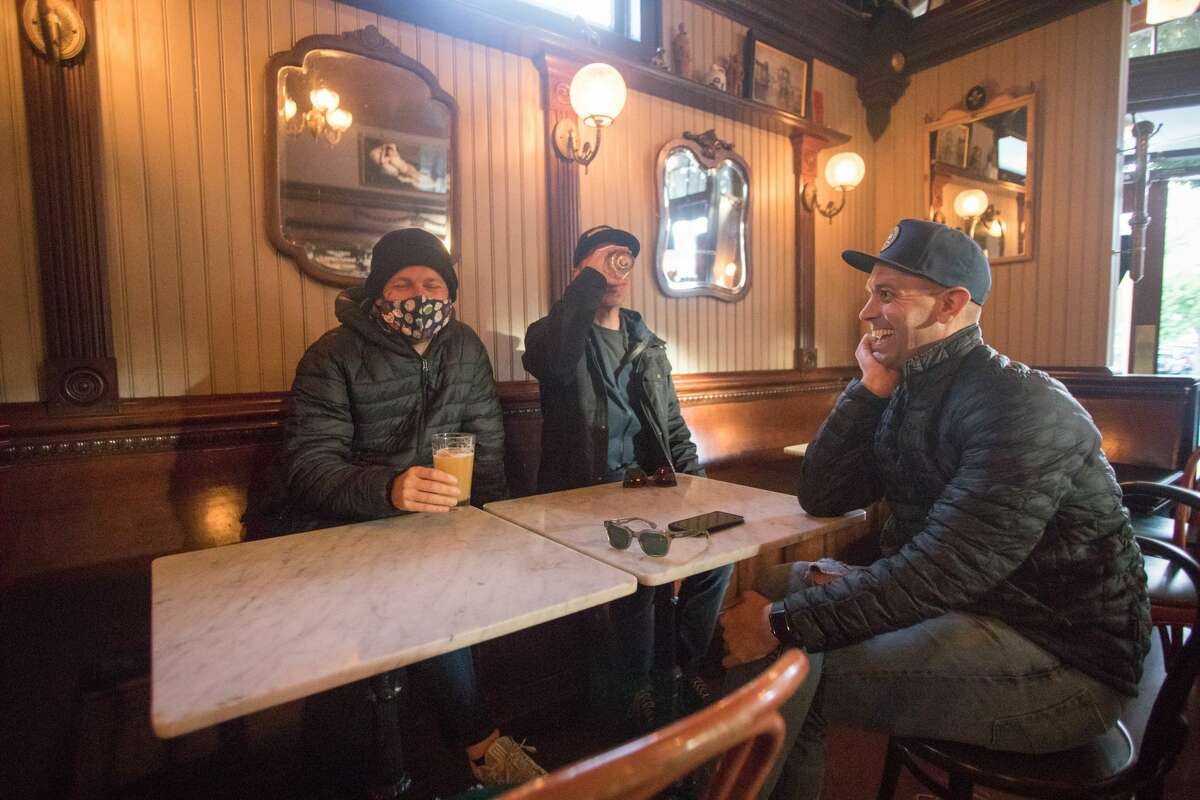 From left to right, Jeremiah Botchlet, Patrick Houck and Luke Roy meet with beer on May 6, 2021 at Shotwell's Saloon in San Francisco.  For the first time since the COVID-19 shutdown began, guests were able to drink in an indoor bar in March 2020.