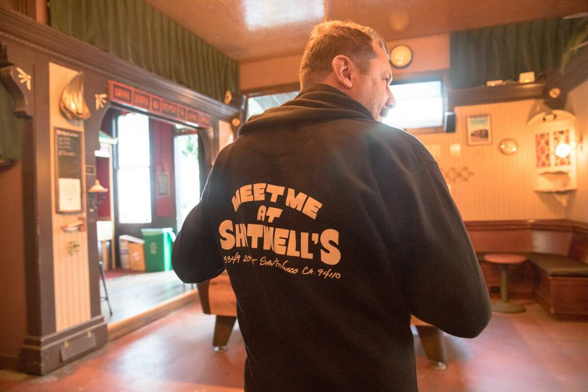 Josh Ziering shows off a Shotwell's Saloon hoodie he bought to support the bar during the San Francisco pandemic on May 6, 2021.  Guests were able to drink inside a bar for the first time since the COVID-19 shutdown began in March 2020.