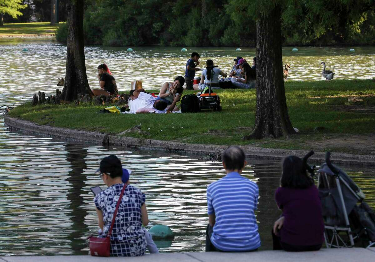 People relax by McGovern Lake on Thursday, May 6, 2021, at Hermann Park in Houston.