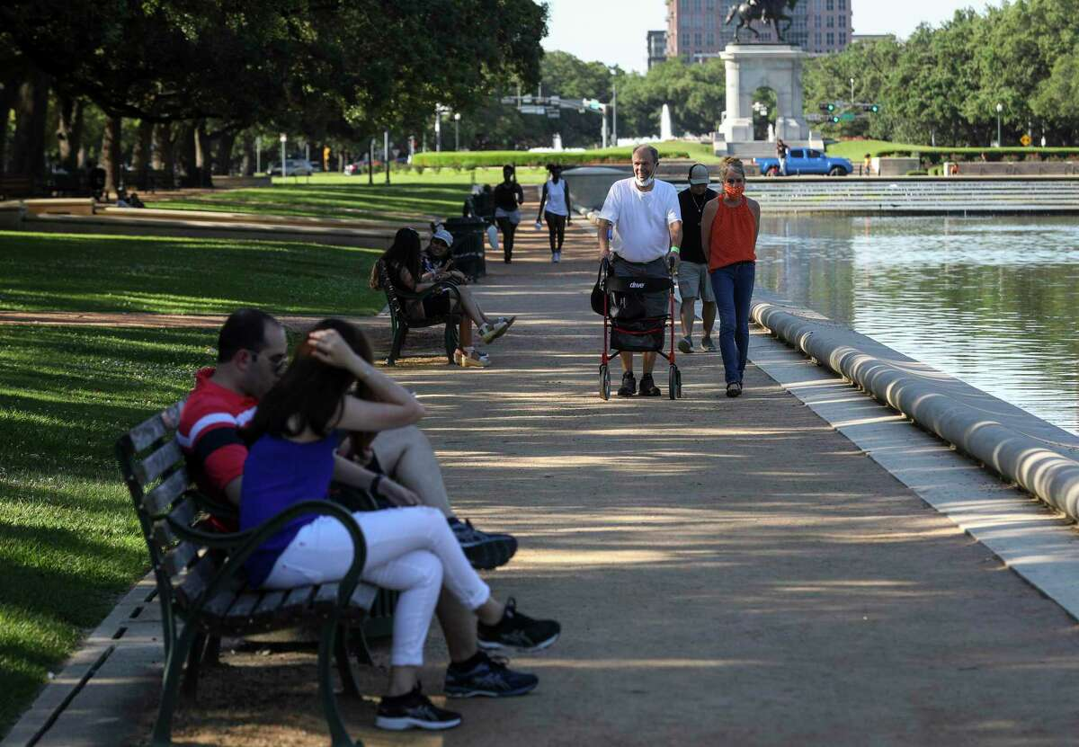 Tom Stewart and his wife Gayle walk along the Mary Gibbs and Jesse H. Jones Reflection Pool on Thursday, May 6, 2021, at Hermann Park in Houston. The pair said they had worn masks since before the COVID-19 pandemic because Tom has leukemia. He said he believes it's usually safe to spend time outdoors.