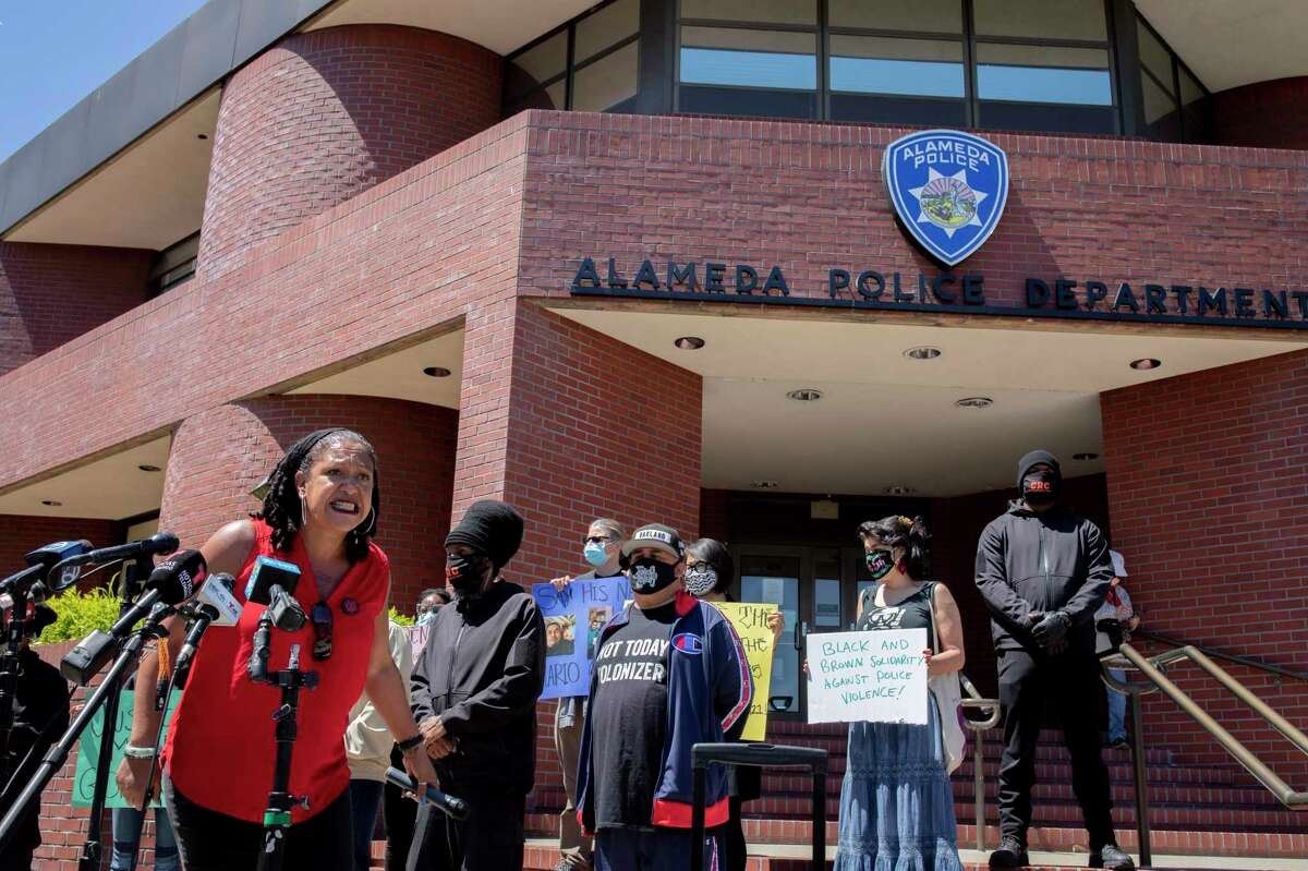 Cat Brooks, with the Justice Teams Network, rallies crowd to say Mario Gonzalez's name at Alameda Police Department.