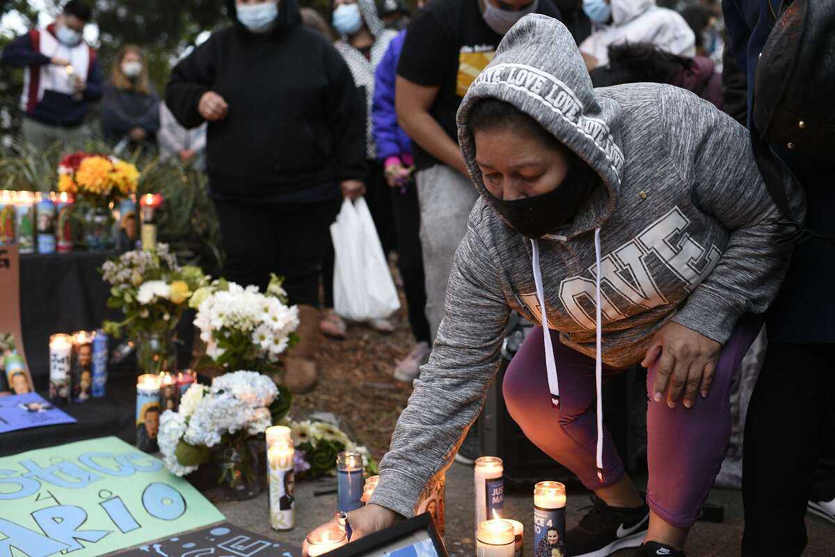 Maria Ortiz of San Leandro places a candle at an altar after an April 21 press conference to demand answers from Alameda police about the death of Mario Gonzalez.