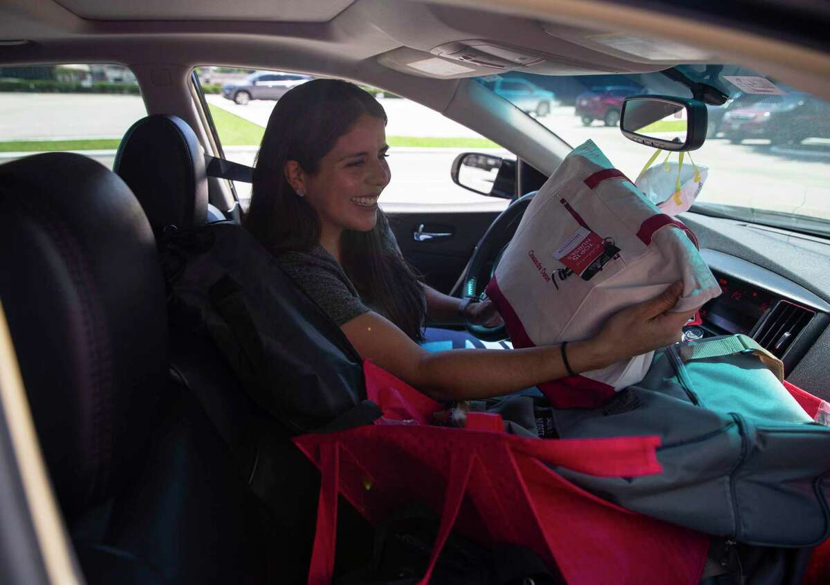 Nurse Cassandra Duran looks at a swag bag with her name on it at the Houston Chronicle's Salute To Nurses drive-thru event Thursday, May 6, 2021, in Houston.