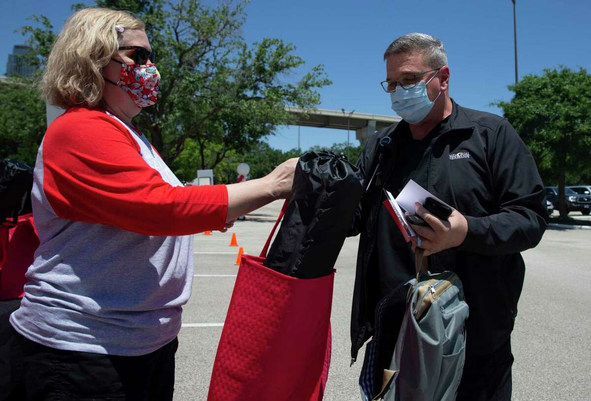 Memorial Hermann nurse Gregg Shoemaker collects swag bags from Houston Chronicle employee Kathy Haveman at the Houston Chronicle's Salute To Nurses drive-thru event Thursday, May 6, 2021, in Houston.
