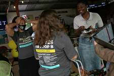 Ananda Tomas, from left, deputy director of Fix SAPD, Michelle Tremillo, executive director of Texas Organizing Project, and Oji Martin, co-founder of Fix SAPD, react to early voting numbers during a watch party with Fix SAPD and supporters of Proposition B at The Friendly Spot in San Antonio on May 1, 2021.