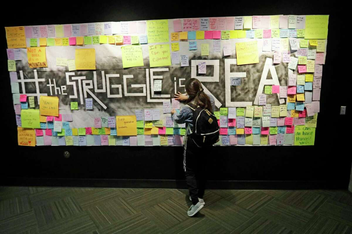 A student in Utah attaches a note to a resiliency board, acknowledging mental health concerns. Stigma is one barrier to treatment for many.