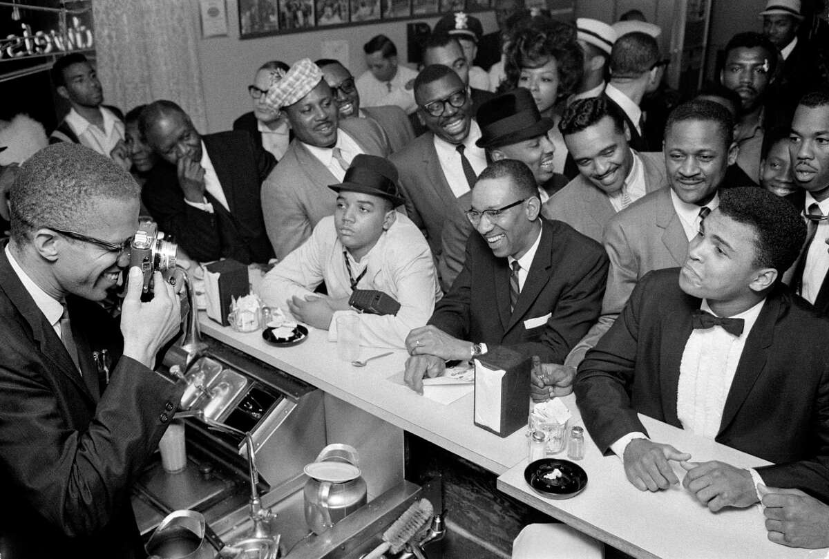 Malcolm X takes a photograph of Muhammad Ali on Feb. 25, 1964 in Miami. Ali was a controversial and conciliatory figure who sparked the nation's conscience. Where is the Ali of today?