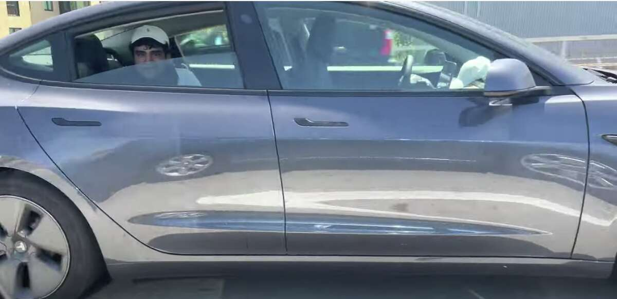 A screenshot of the man sitting in the backseat of his Tesla.