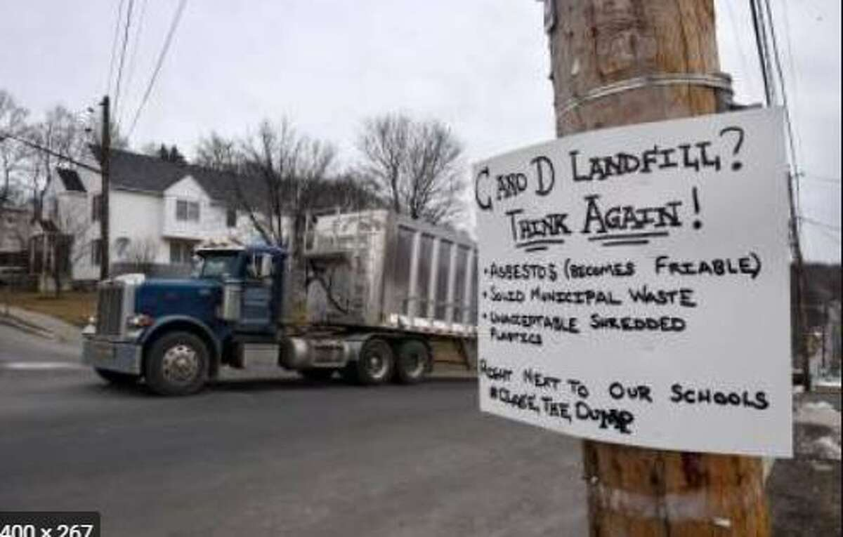 A truck makes its way toward the SA Dunn landfill, near a sign protesting the facility which is in the middle of Rensselaer.