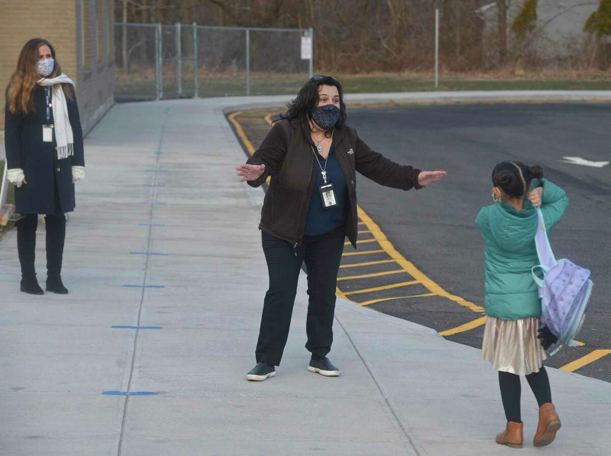 Helena Andrade, ESL bilingual teacher at Stadley Rough Elementary School welcome a returning student. The school started in person learning for the first time since March of last year. Tuesday, January 19, 2021, in Danbury, Conn.