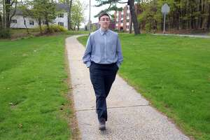 Jude Reid walks near their home in New Britain on Tuesday. Reid is in the process of being vaccinated for COVID-19.