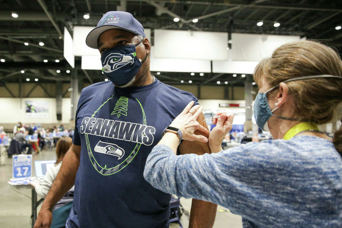 Cleveland Hughes wears Seahawks gear as he gets the Pfizer Covid-19 vaccine from Andrea Barnett during opening day of the Community Vaccination Site, a collaboration between the City of Seattle, First & Goal Inc., and Swedish Health Services at the Lumen Field Event Center in Seattle, Washington on March 13, 2021.