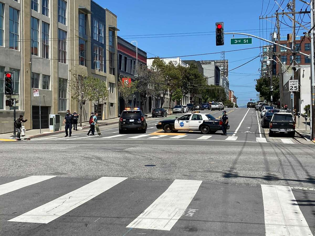 Police cars staged on Third Street in San Francisco following a police shooting in the area.