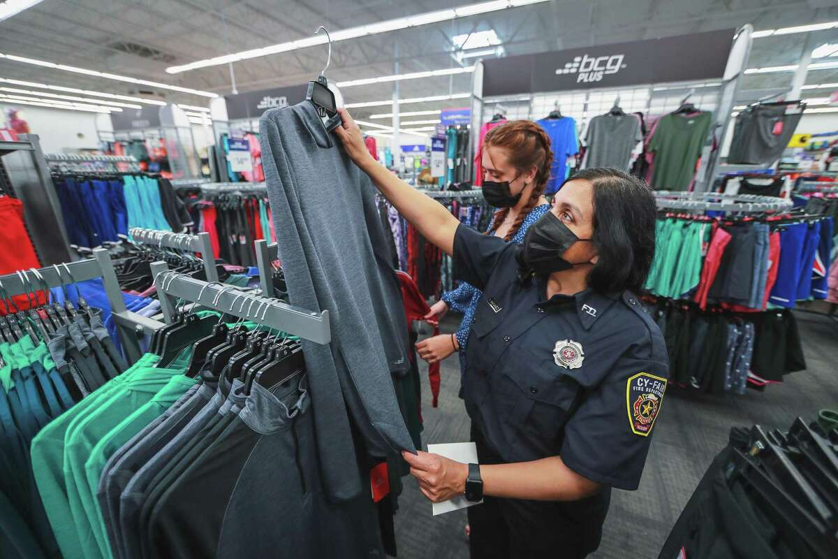 Debra Vasquez holds up a nice shirt while her daughter Sarah Wynn thumbs through more clothes looking for the right sizes for her mother who is a firefighter with the Cypress Fairbanks Fire Department.
