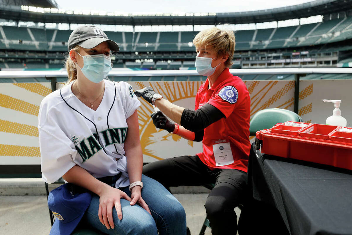 Sydney Porter of Bellevue, Wa. receives her COVID-19 vaccination from Kristine Gill, with the Seattle Fire Department's Mobile Vaccination Teams, before the game between the Seattle Mariners and the Baltimore Orioles at T-Mobile Park on May 05, 2021 in Seattle, Washington.