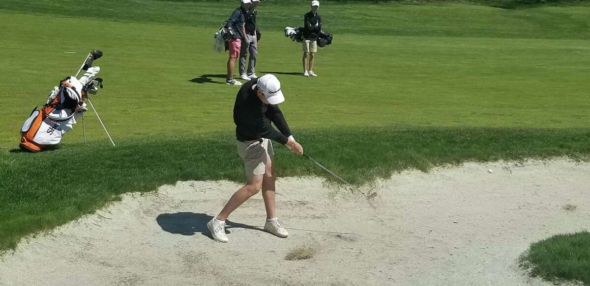 Shelton's Kyle St. Pierre hit a shot out of a fairway bunker on the first hole at Madison Country Club.