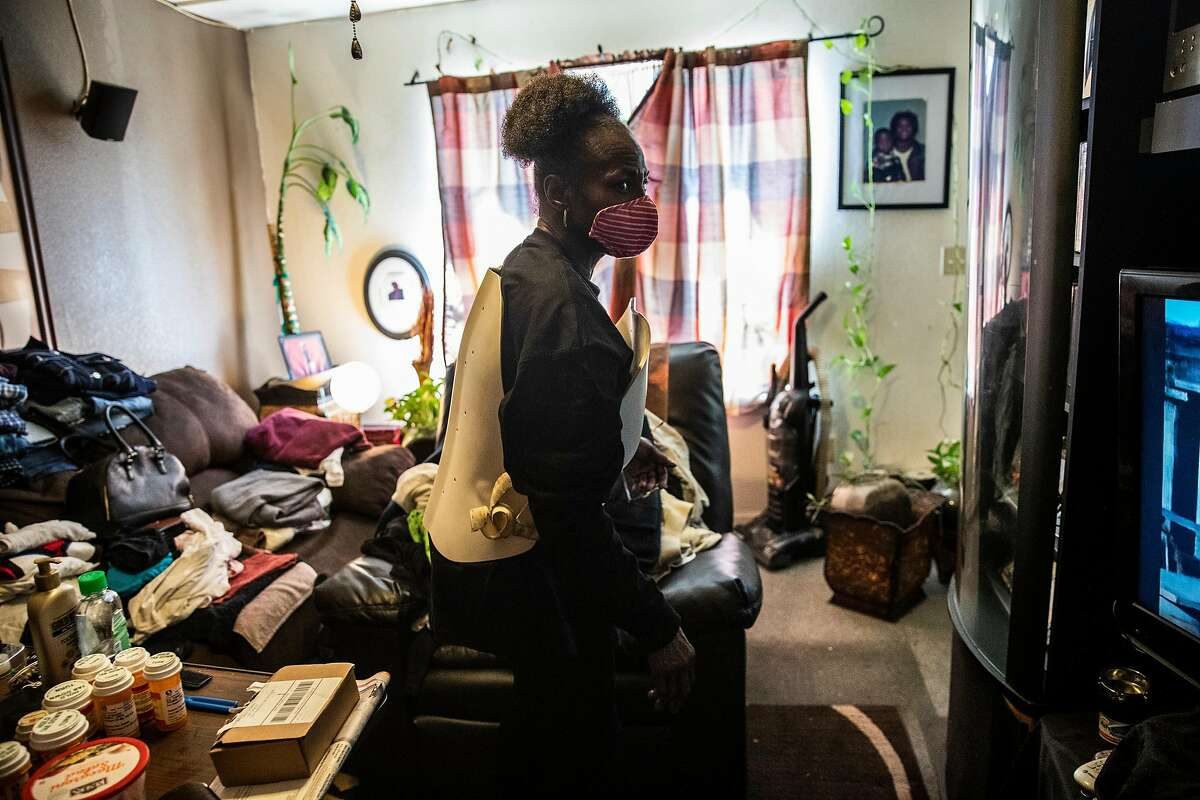 Linda Thomas, wearing a back brace for her injured back, walks inside her home at Plaza East Apartments in San Francisco, Calif. May 5, 2021. Residents of the complex have been voicing concerns for years about its unsafe living conditions stemming from a backlog of deferred maintenance, while worrying the city's plan to repair and transform the complex into mixed-income housing will further gentrify the area.