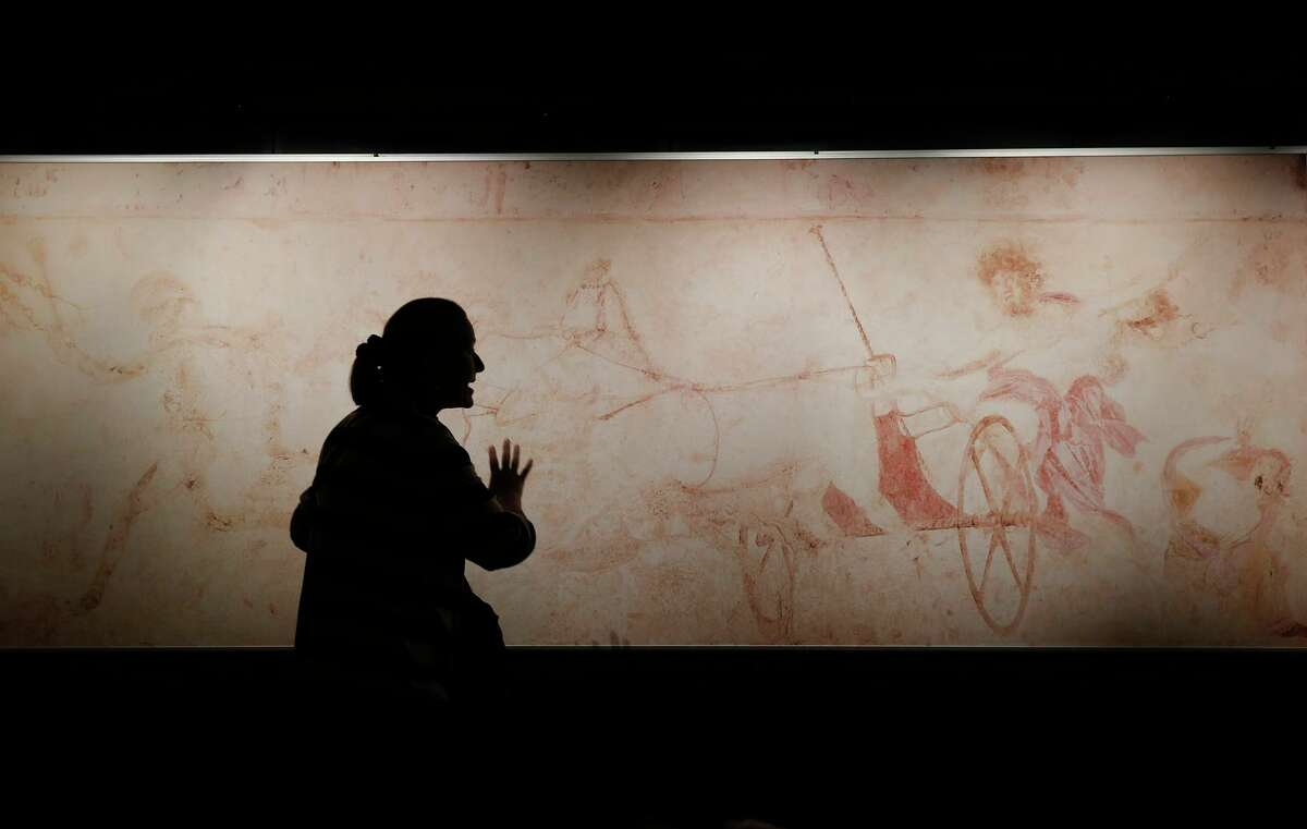 A schoolteacher explains the myth of Persephone in front of a wall painting of Hades abducting Persephone.