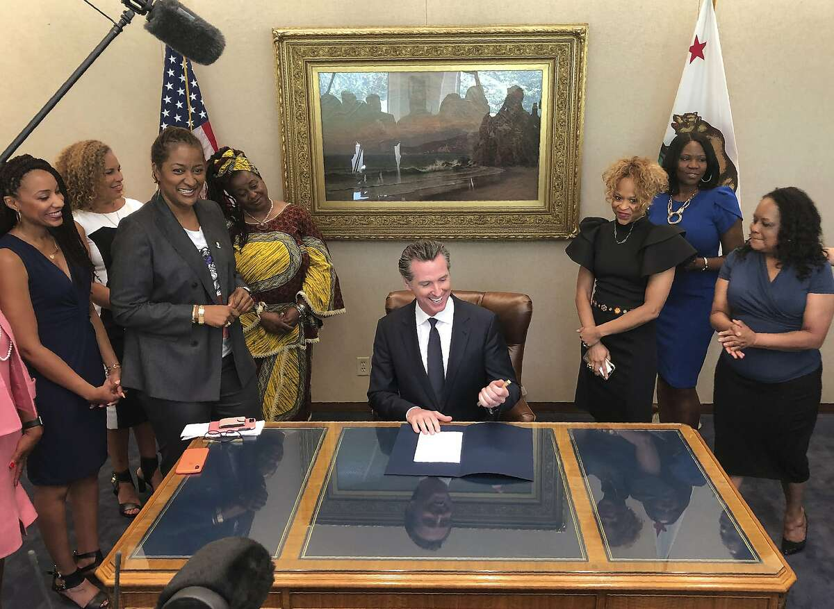California Gov. Gavin Newsom, middle, signs State Bill, SB-188 Discrimination: hairstyles by state Sen. Holly Mitchell of Los Angeles, third from left, that bans workplace and school discrimination against black people for wearing natural hairstyles, including locks and braids. Newsom signed the law, the first of its kind by any state, at the Capitol in Sacramento on Wednesday, July 3, 2019. Federal courts, though, have regularly ruled that hairstyles do not count as an