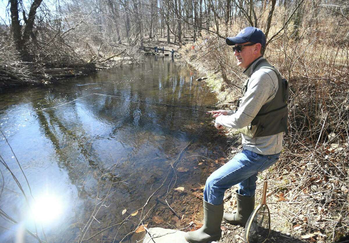 A fisherman tries out a new fishing spot on the Mill River in Fairfield on Sunday, March 21, 2021.