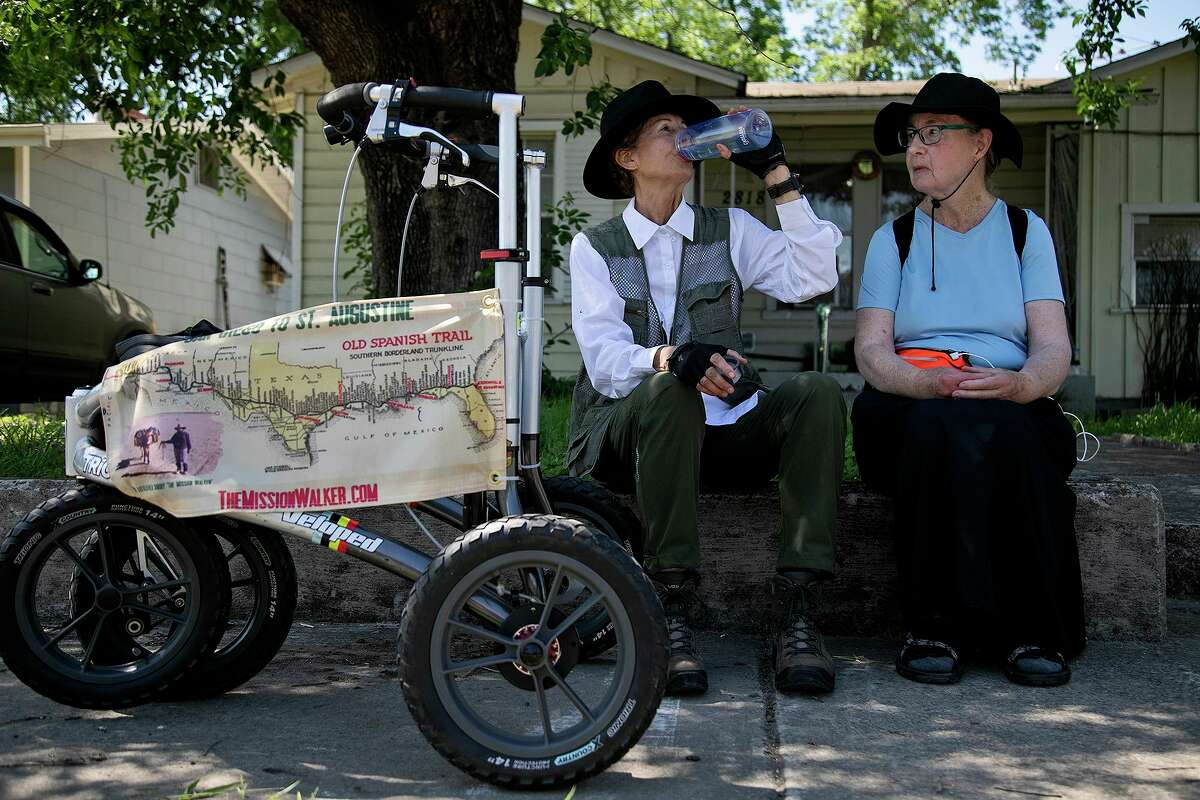 Edie Littlefield Sundby, left, of San Diego, CA, and Joyce Blue Summers, of Alamogordo, NM, take a break in the shade to eat and drink on East Houston Street as they follow the Old Spanish Trail through San Antonio on May 7, 2021.