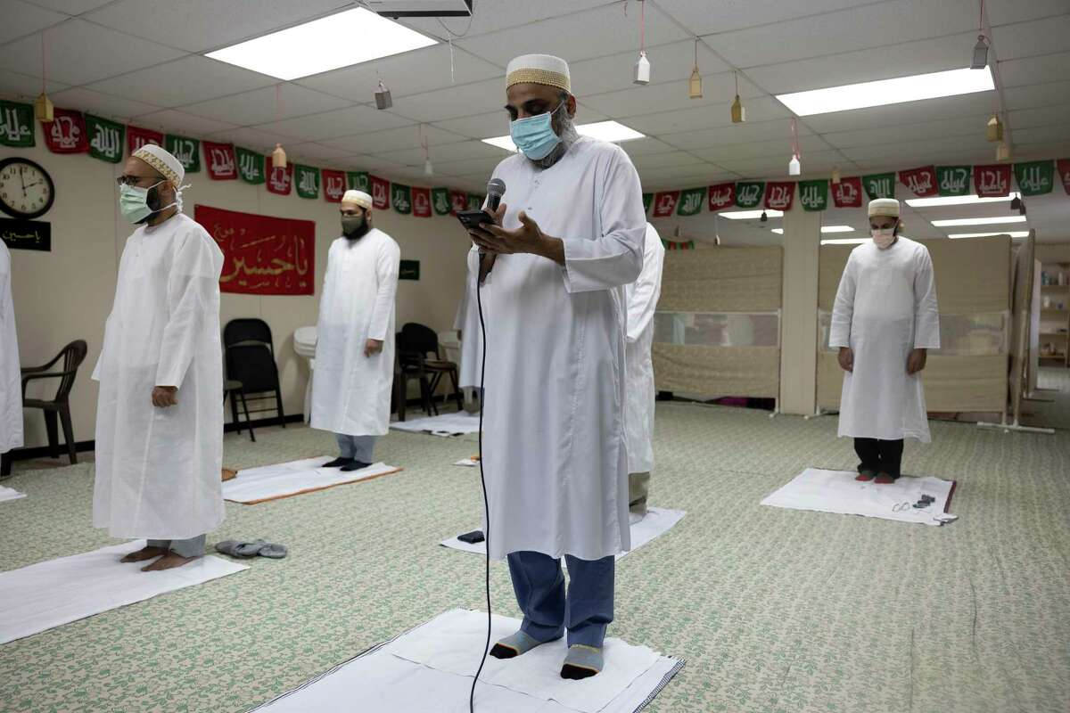 Dr. Ali Bhuriwalla, center, reads prayers as members of the Dawoodi Bohra community come to pray during Ramadan, Friday, May 7, 2021, in the Woodlands. Due to COVID-19, only members who have been fully vaccinated are able to participate during prayers at the house of worship.