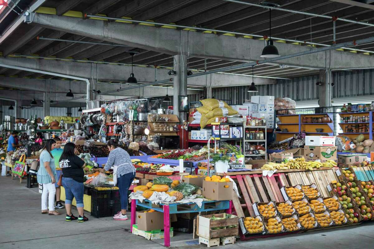 Shoppers browse items for sale at The Houston Farmer's Market Monday, May 3, 2021 in Houston. Construction on the revamped site is finished and vendors have begun moving in. The location will also include restaurants and a green space next to the market. The pillars in the area are from a former highway project by TXDOT.