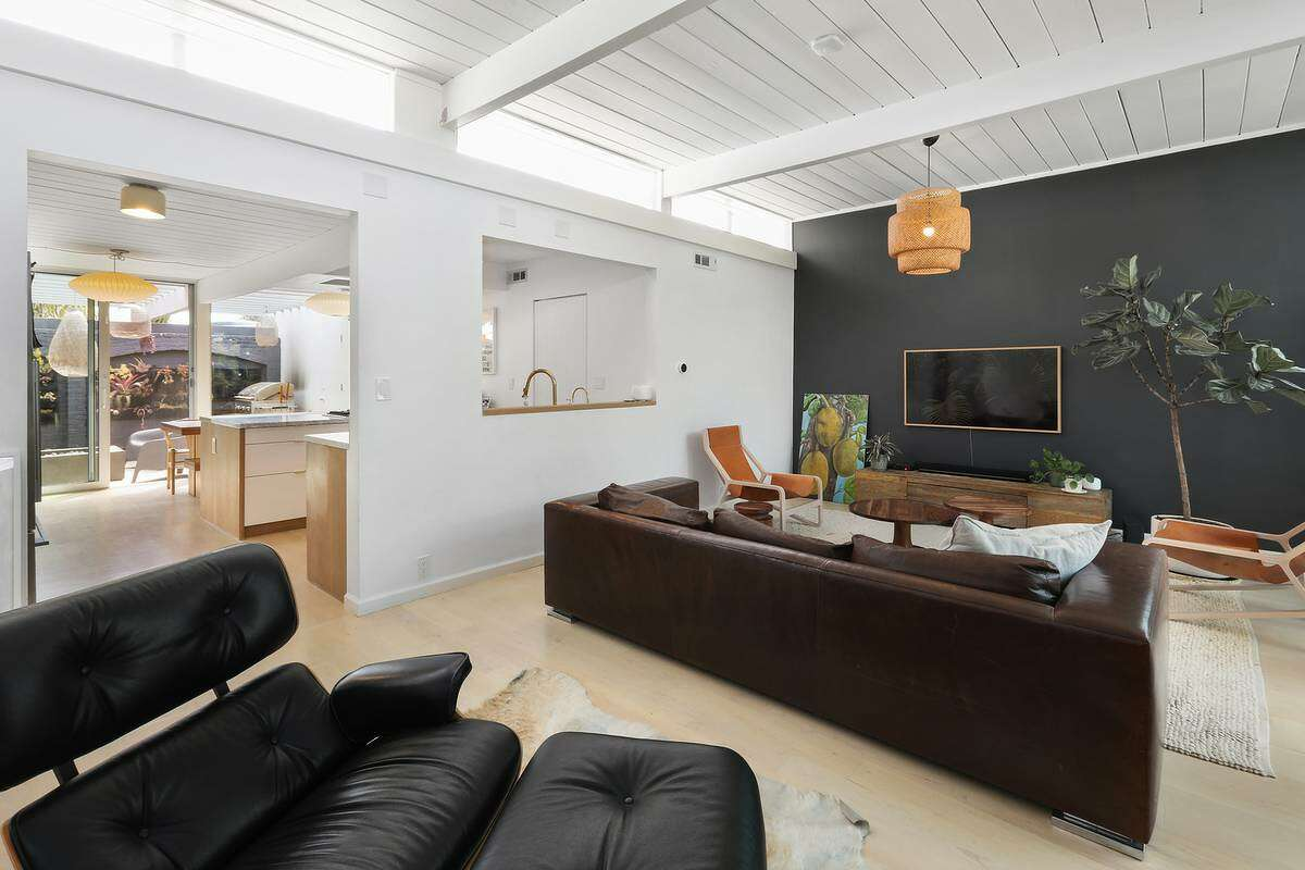 A living room is set next to the kitchen with a nearby nook with bookshelves.