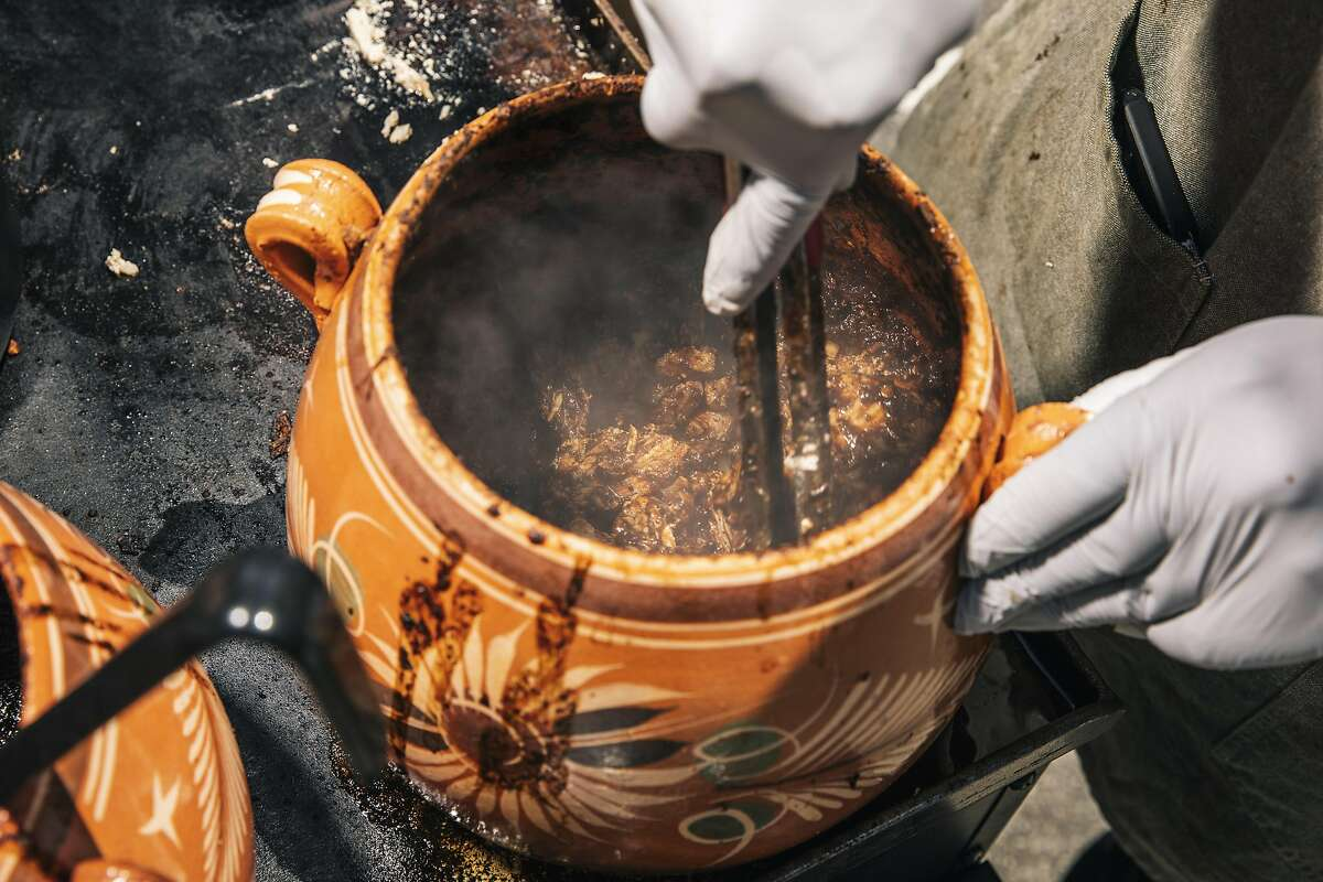 Nomar Ramirez of Molcaxitl Kitchen cooks turkey mole in a ceramic pot in homage to the ones his grandparents cooked with in Mexico.