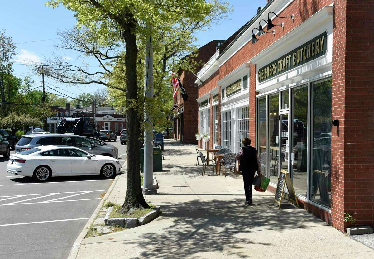 A woman walks on the sidewalk in the retail hub of downtown Cos Cob in Greenwich, Conn. Thursday, May 6, 2021.