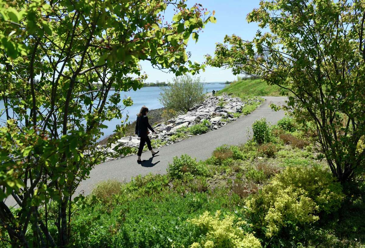 A woman walks through Cos Cob Park overlooking the Long Island Sound in the Cos Cob section of Greenwich, Conn. Thursday, May 6, 2021.